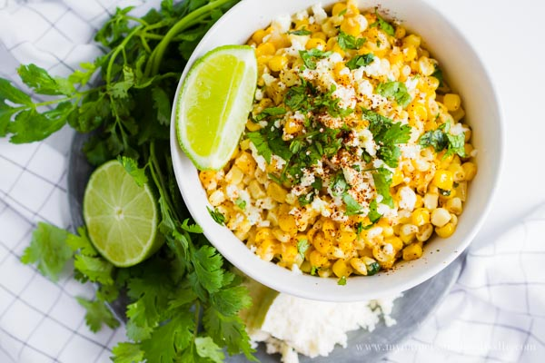 A white bowl full of grilled corn topped with cheese, chopped cilantro and lime wedges on the side.