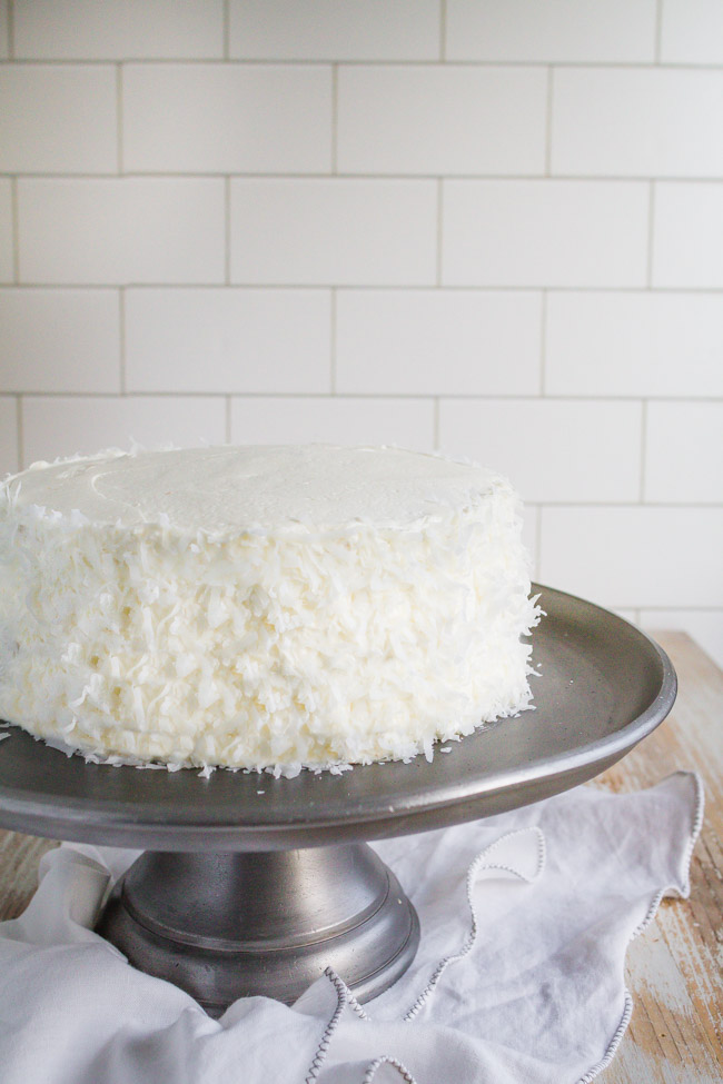 Coconut Cream Cake frosted with coconut butter cream on a silver cake stand