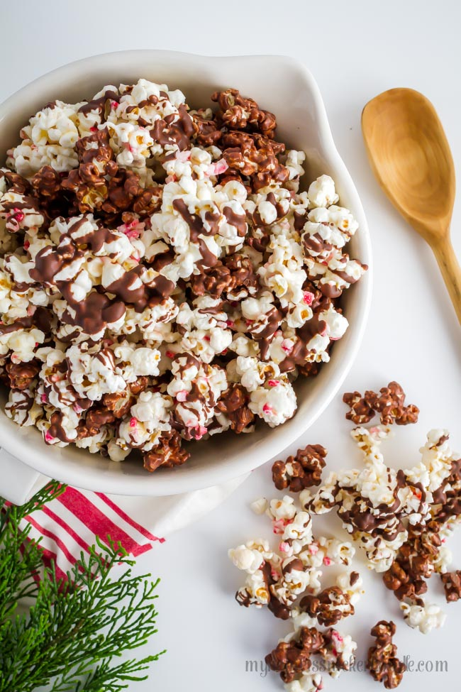 Peppermint Bark Popcorn drizzled with mint chocolate and peppermint candy in a bowl.