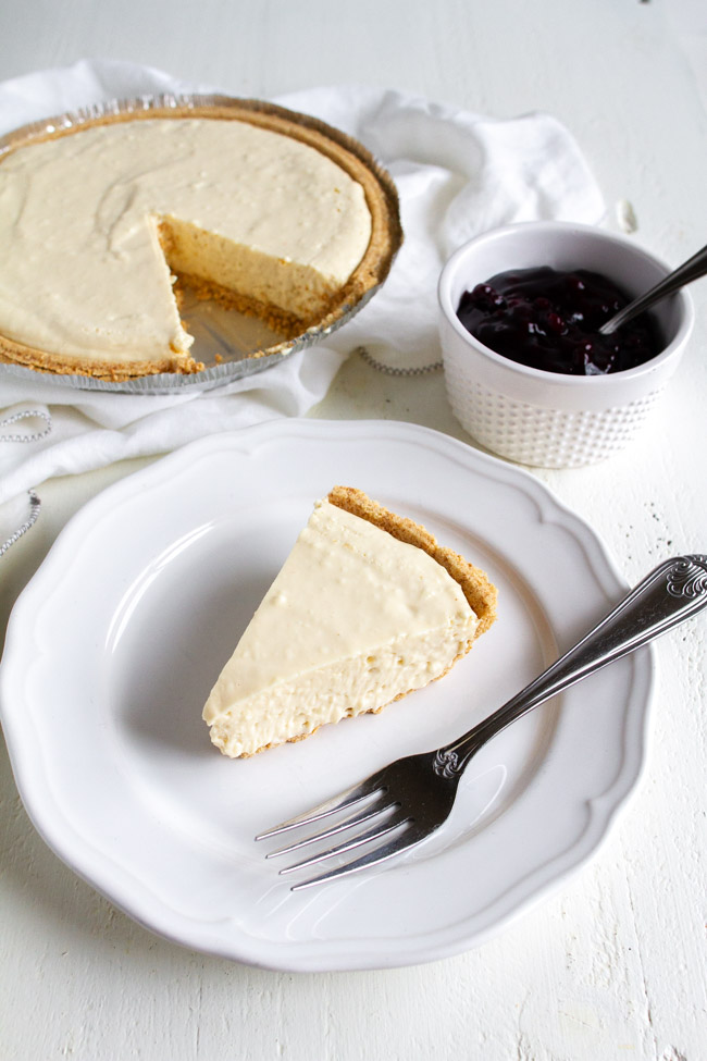 A plain slice of no bake cheesecake on a white plate with a fork.