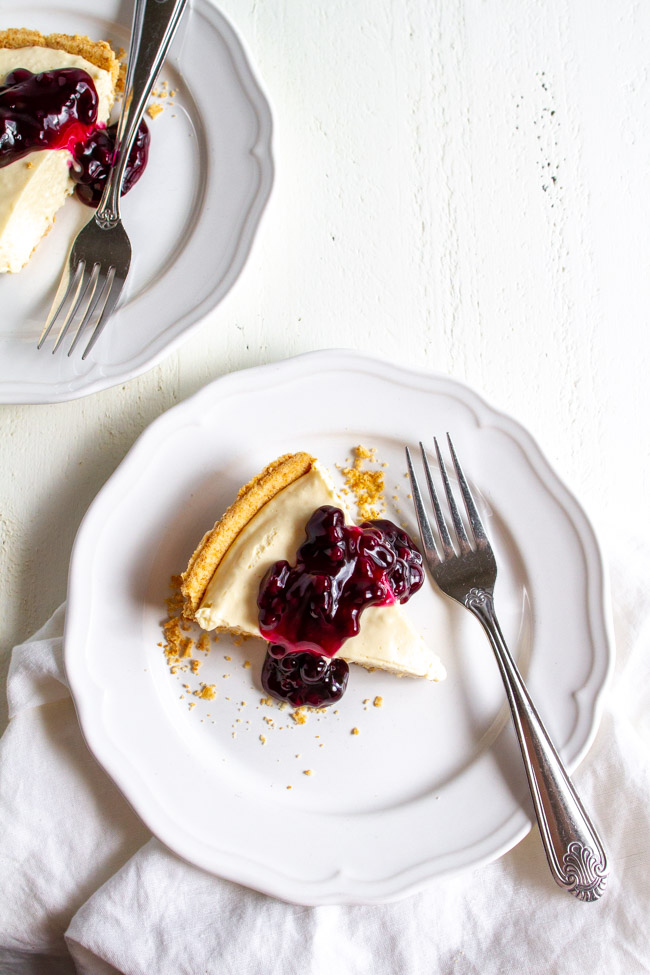 Two slices of blueberry no bake cheesecake on a white plates.