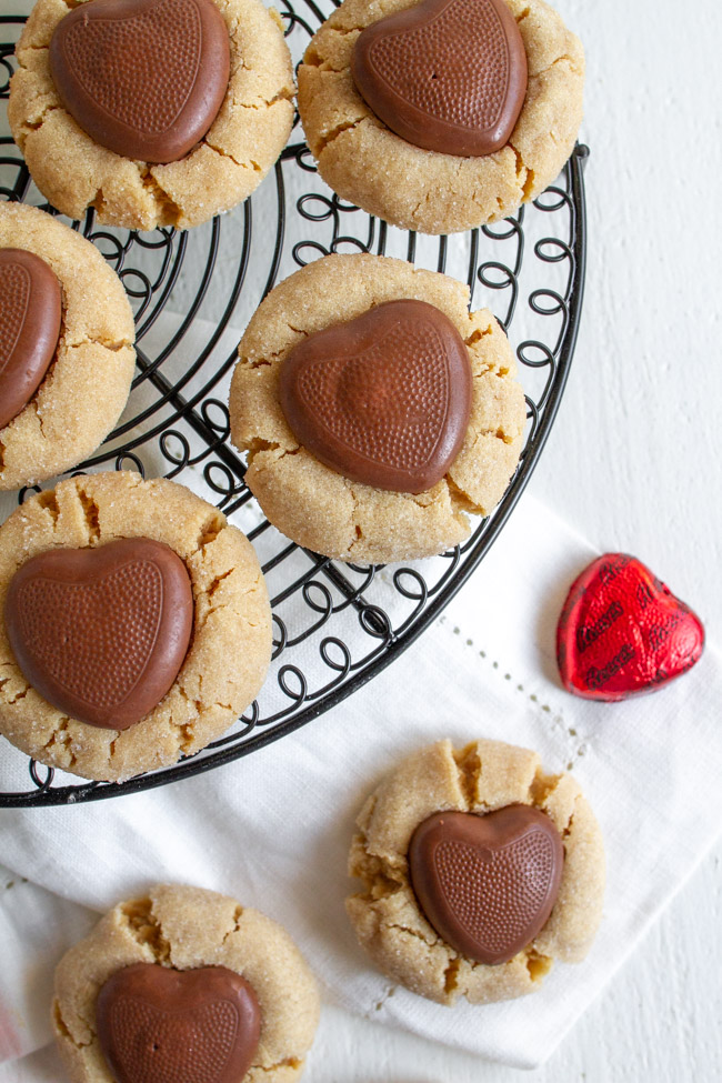 Peanut Butter Blossom with a chocolate heart on a black wire cooling rack