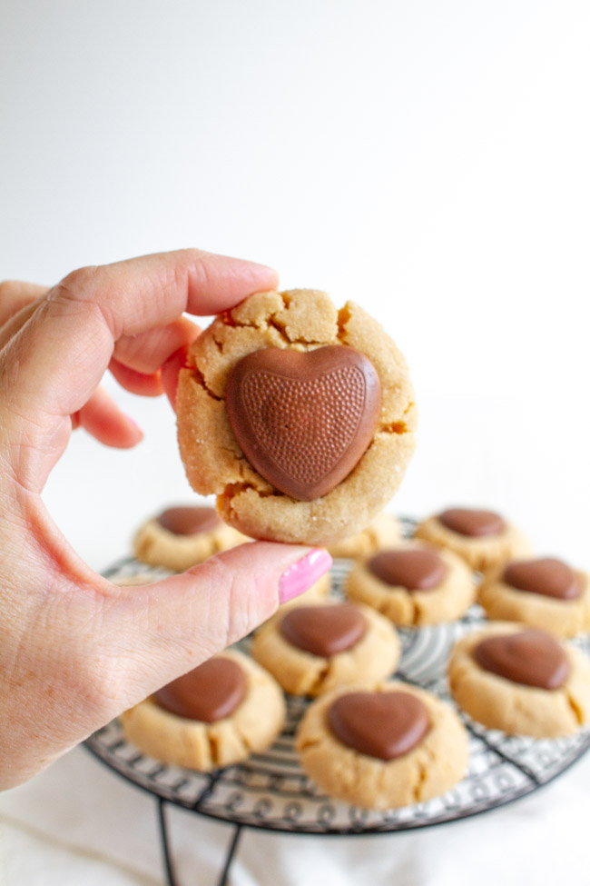 A hand holding a Peanut Butter Blossom with a chocolate heart