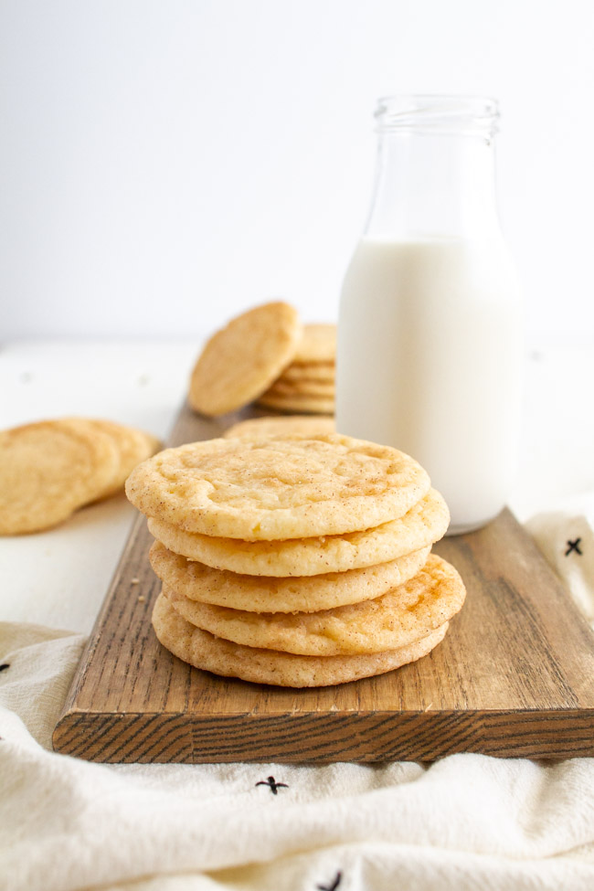 Snickerdoodle Cookies on a wooden tray with a glass of milk.