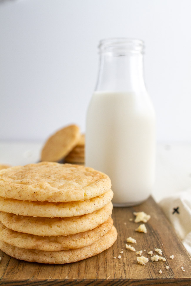 Stacked up Snickerdoodles on a wood tray with a glass of milk.