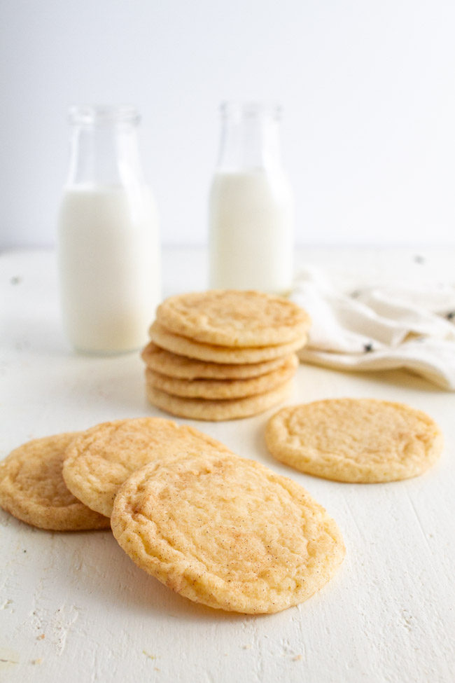 Stacked up Snickerdoodle Cookies on a white table with two glasses of milk.