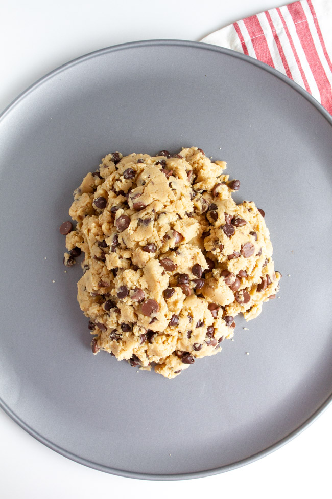 Chocolate Chip Cookie Dough in a pile on a silver pizza pan.