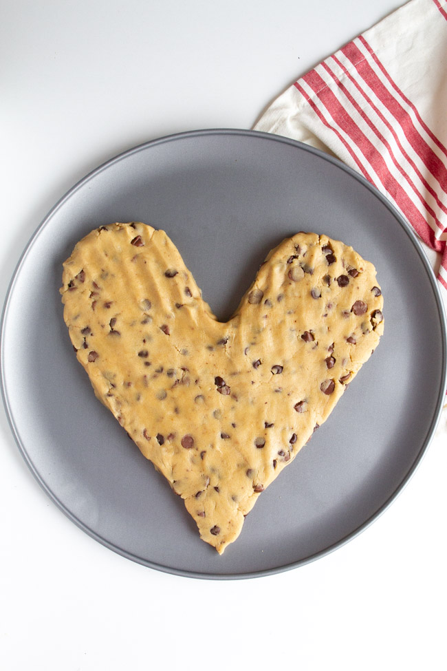 Heart shaped chocolate chip cookie dough on a silver pizza pan.