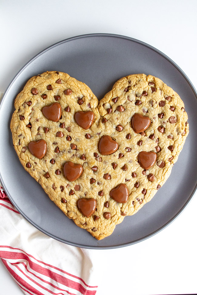 Heart Shaped Chocolate Chip Cookie with melted heart chocolates on a pizza pan.
