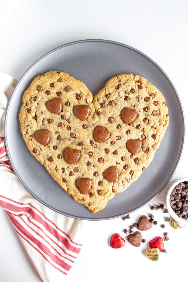 Heart Shaped Chocolate Chip Cookie with heart chocolates on a pizza pan.