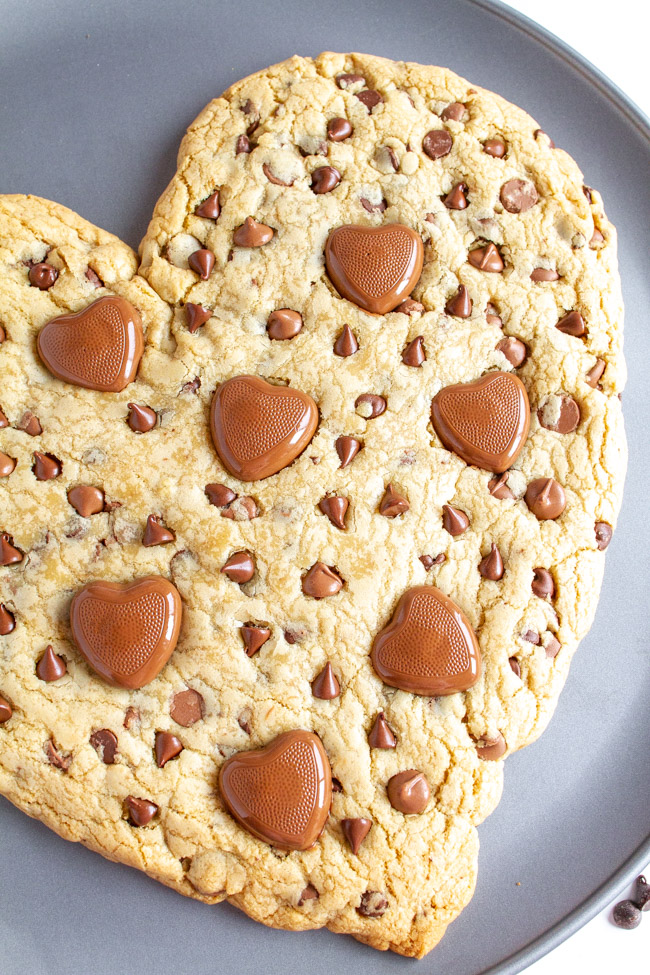 Close up of a Heart Shaped Chocolate Chip Cookie with heart chocolates on a pizza pan.