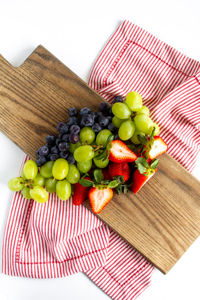 Strawberries, blueberries and grapes on a wood cutting board