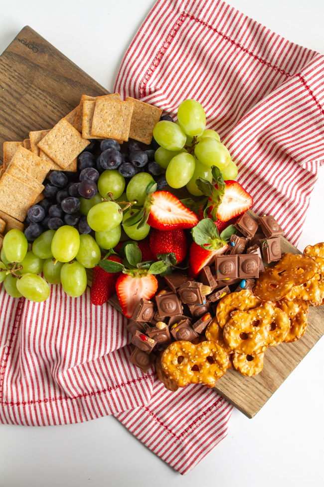 Crackers, fruit and chocolate on a wood board