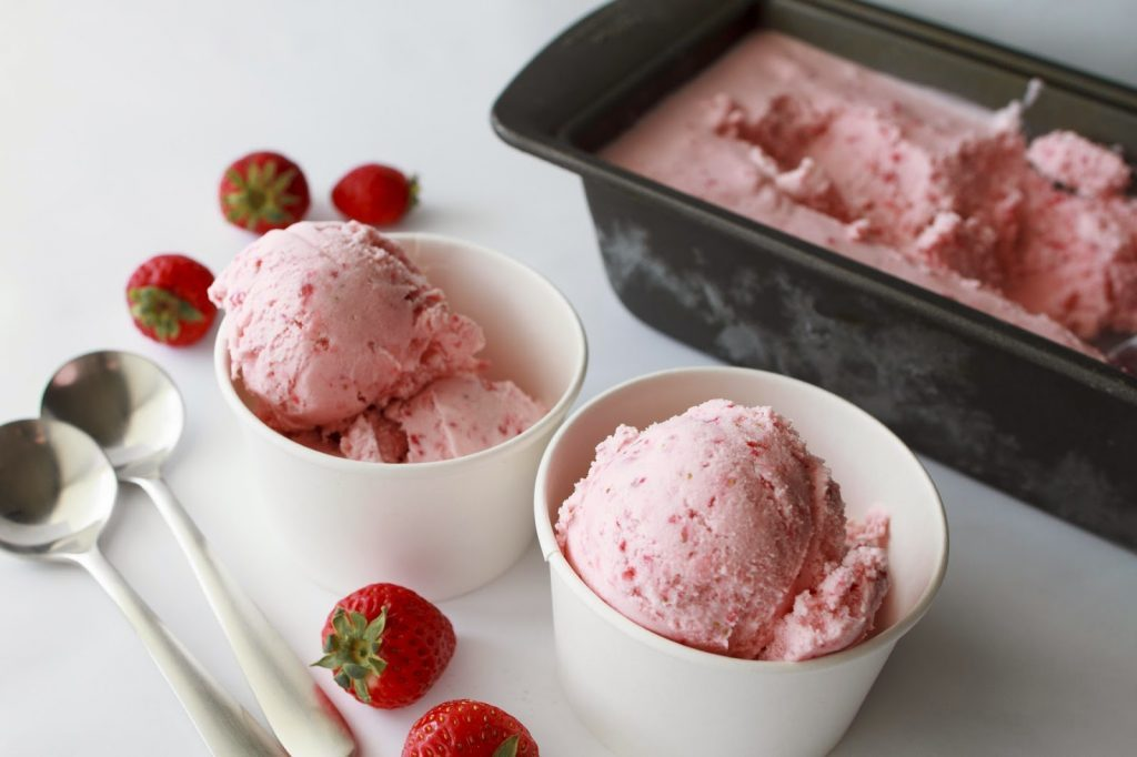 Two white bowls with strawberry ice cream and two spoons.