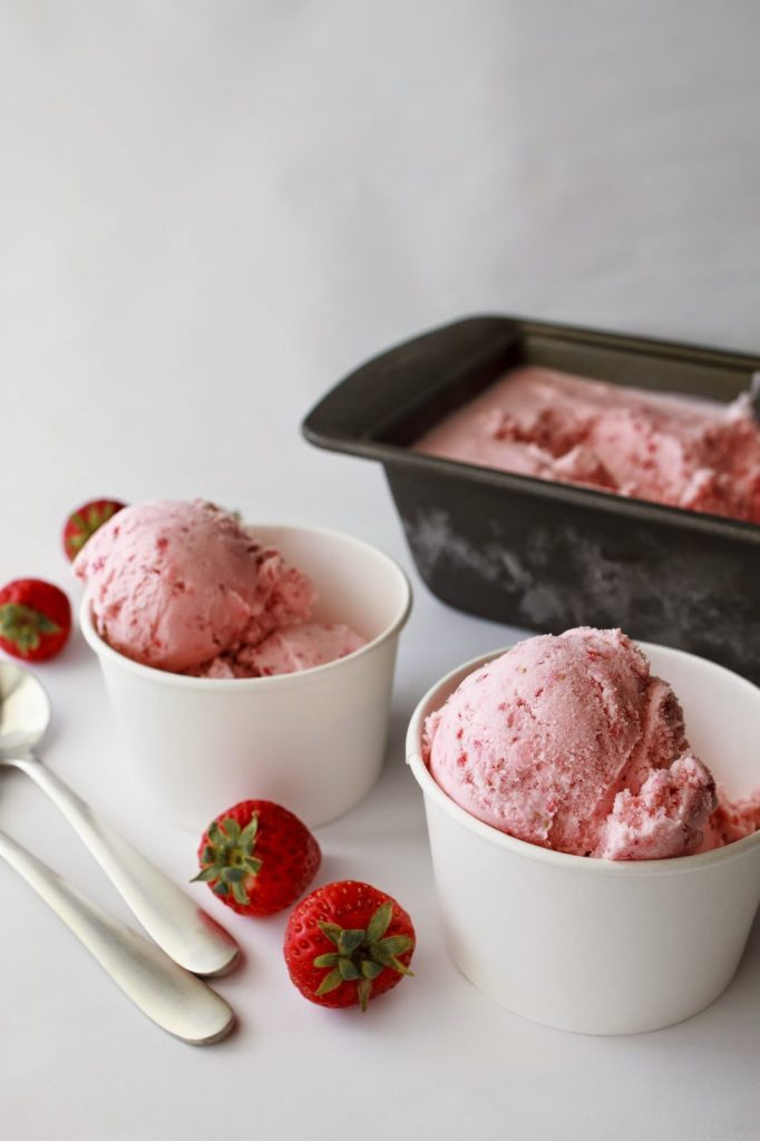 Two white paper bowls with strawberry ice cream on a white table.