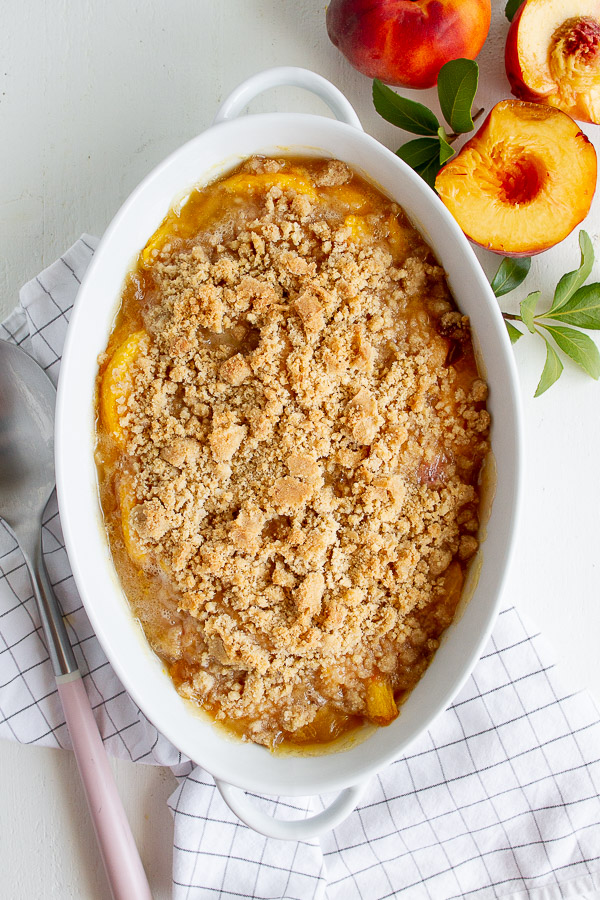 Peach Crisp Recipe served in a white baking dish.