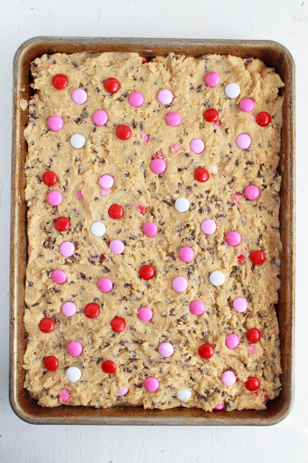 Pink and Red M&M's being added to chocolate chip cookie dough.