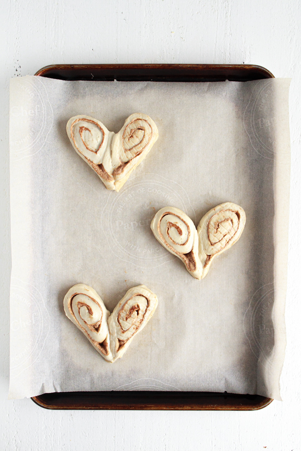 Three heart shaped cinnamon rolls on a parchment lined baking sheet.