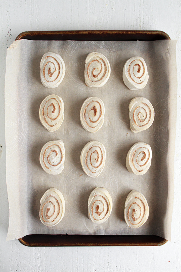 Thawing out cinnamon rolls on a parchment lined baking sheet.