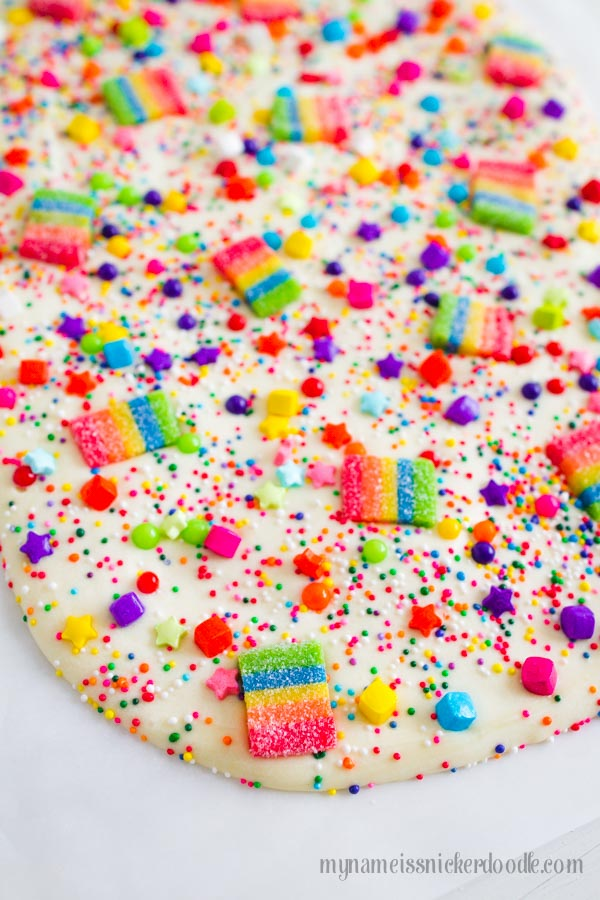 Rainbow sprinkles and gummies over melted white chocolate.
