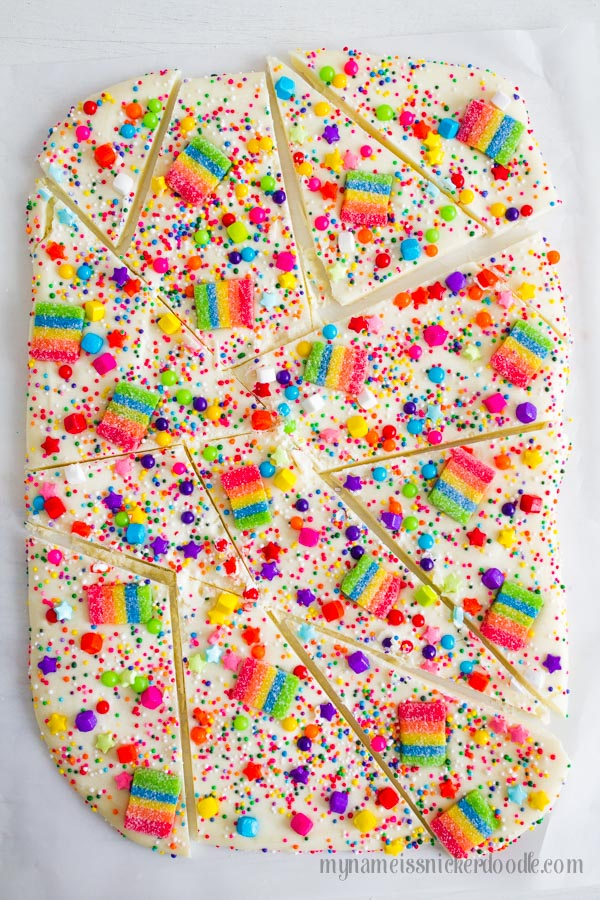 White Chocolate candy bark with rainbow sprinkles and gummies.