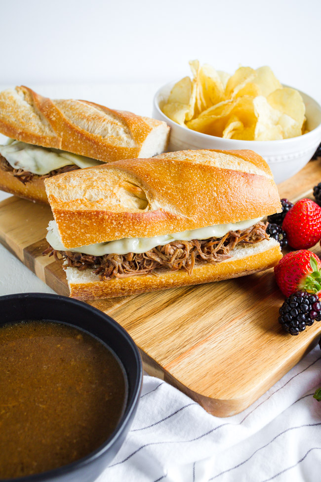 Slow cooker French Dip Sandwiches on a wooden cutting board.