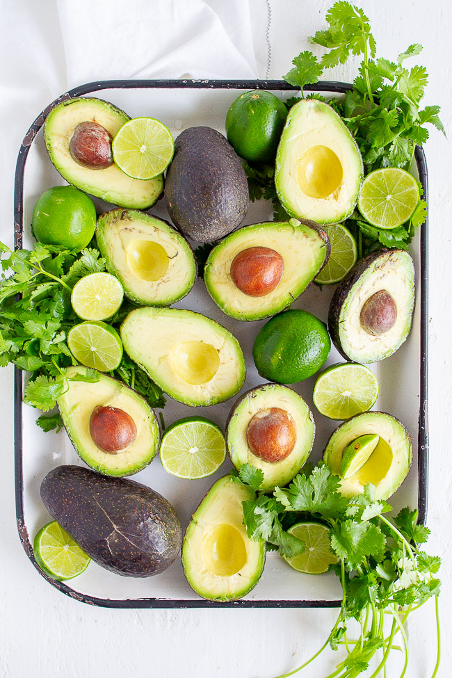 Ripe avocados, cilantro and limes.