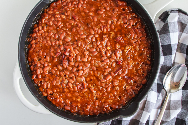 Baked Beans in a black cast iron skillet with a checked napkin.