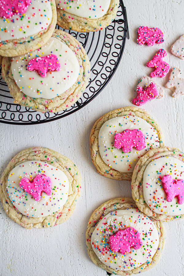 Frosted sugar cookies with sprinkles on a wire cooling rack.