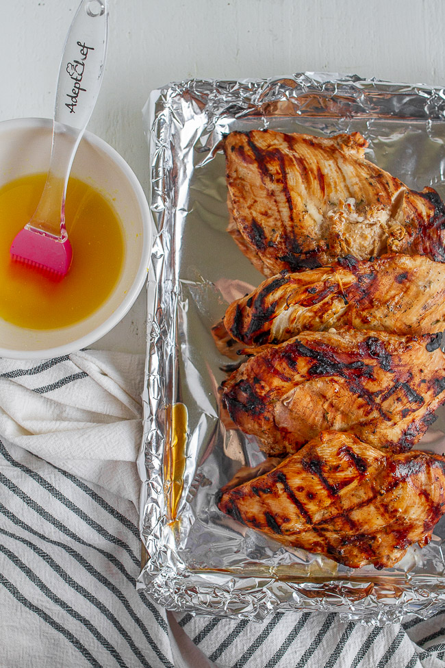 Grilled lemon chicken on a foil lined pan along side a bowl of lemon butter.