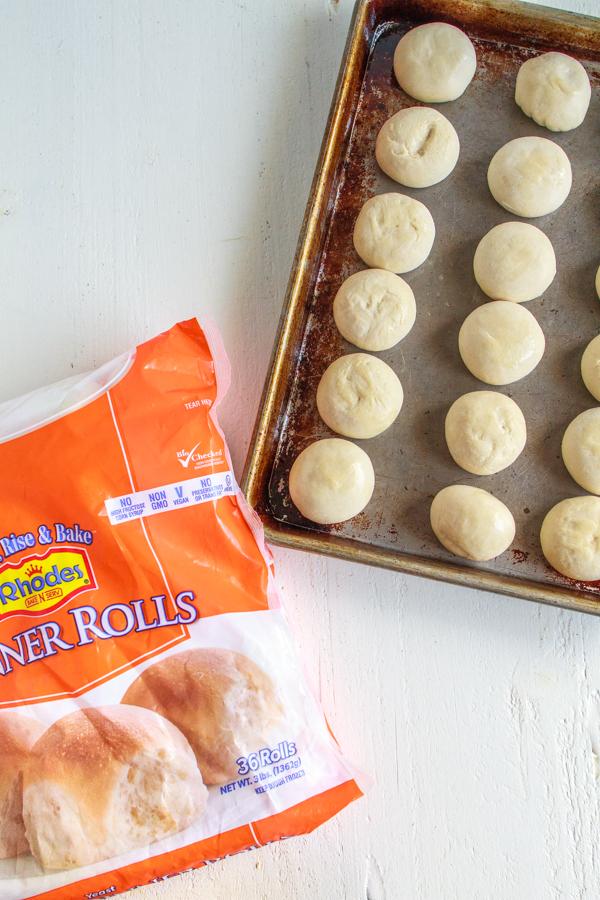 Frozen rolls on a baking sheet.