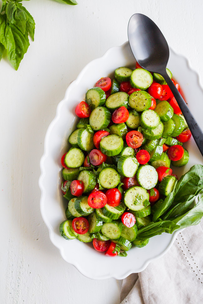 Tomatoes and cucumbers along with fresh basil sliced and tossed in a white dish.