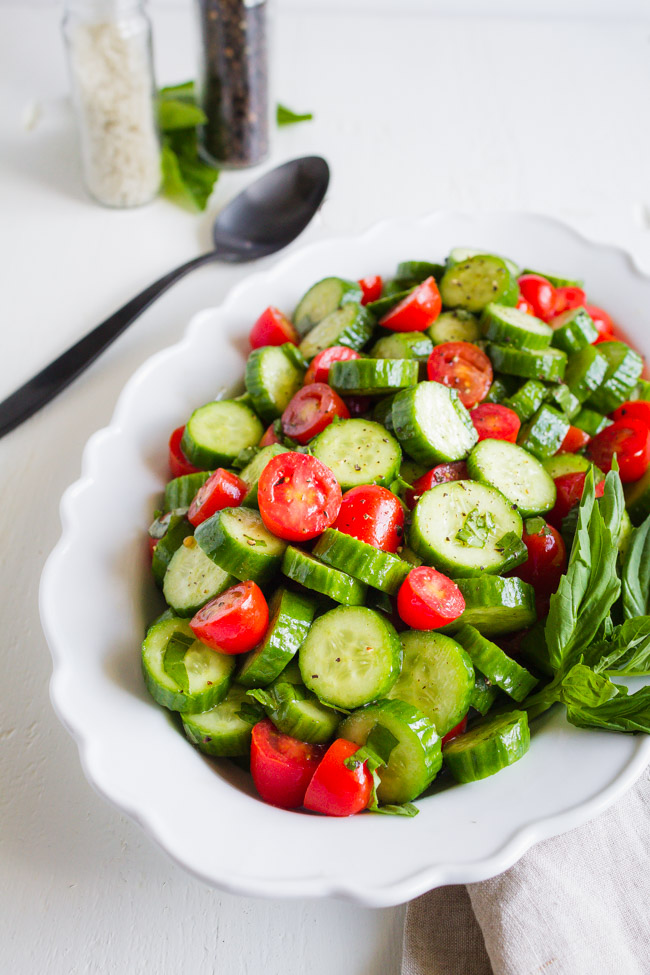 Basil, tomatoes and cucumbers sliced and tossed in a white dish.