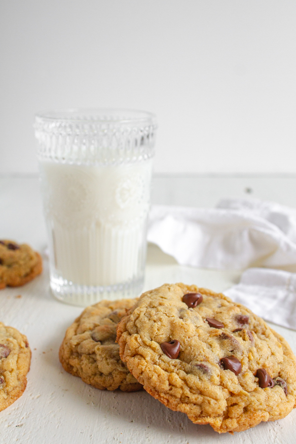 A glass of milk with two chocolate chip oatmeal cookies.