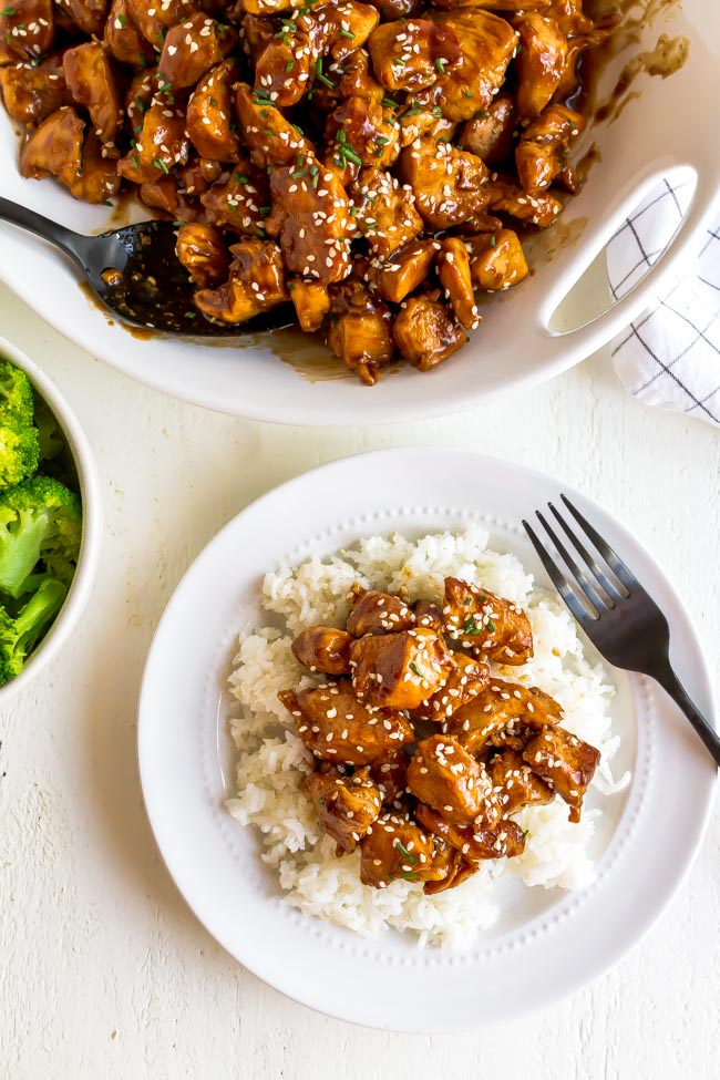 A white bowl with sesame chicken and a plate of rice.