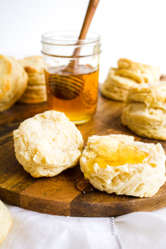 Homemade Flaky Buttermilk Biscuits drizzled with honey.