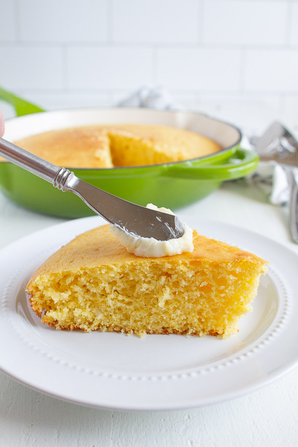 A slice of corn bread slathered with butter.