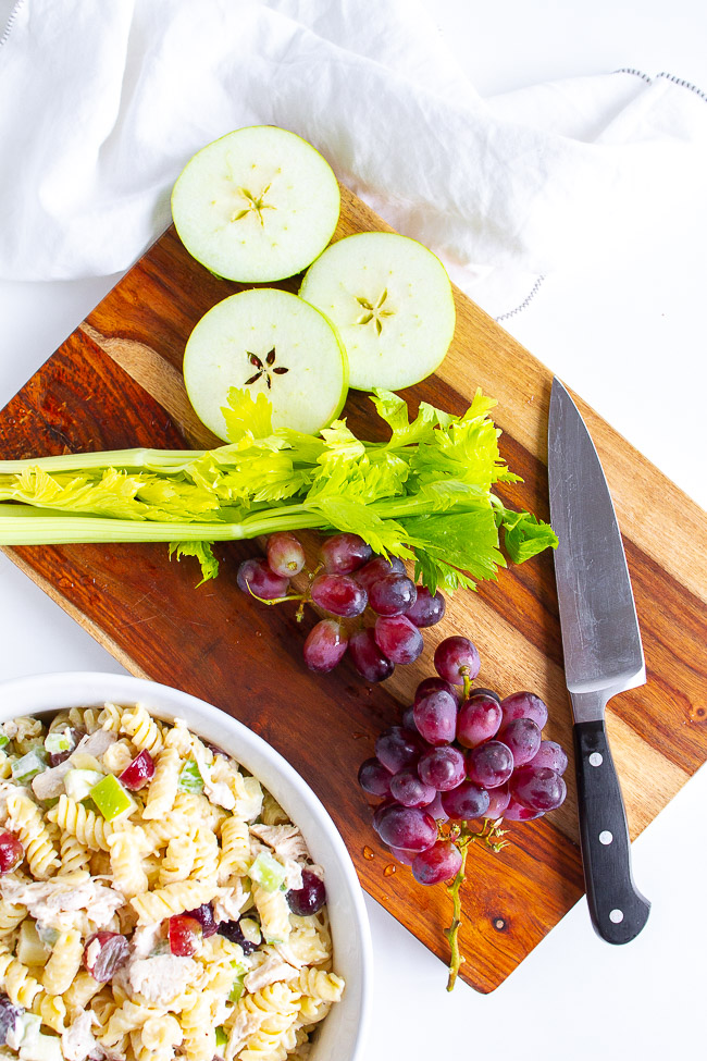 Celery, green apples and purple grapes on a wooden cutting board.
