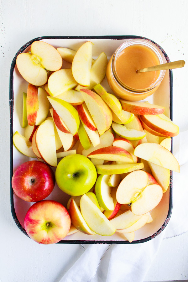 A white platter of sliced apples with a jar of caramel sauce