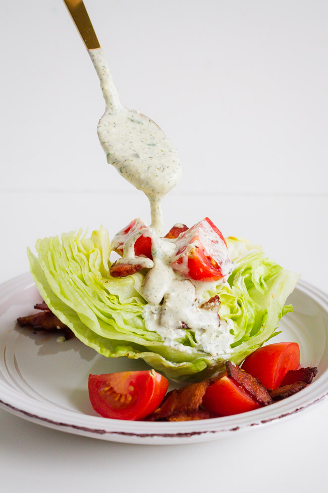 A wedge salad being topped with Homemade Ranch Dressing.