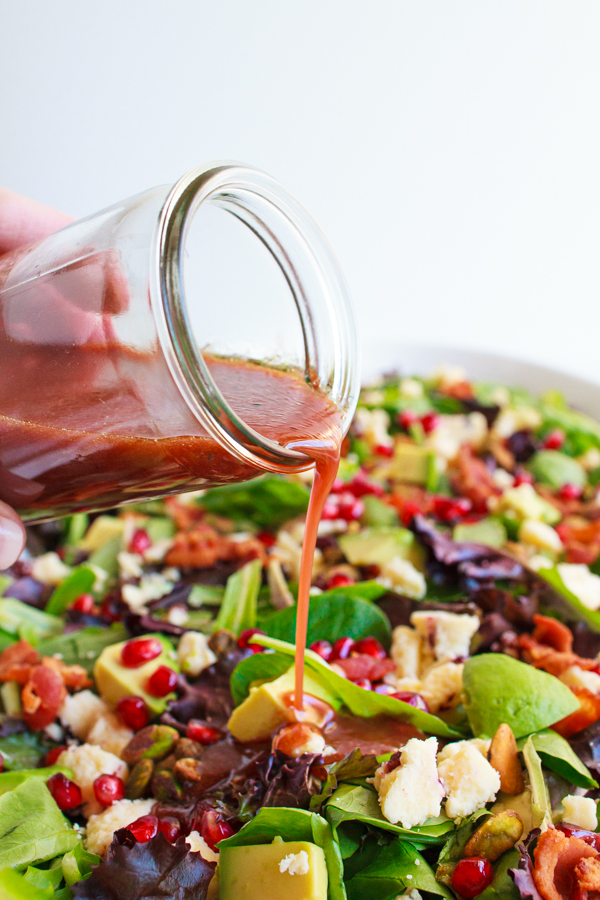 Pomegranate Salad Dressing being poured over a salad.