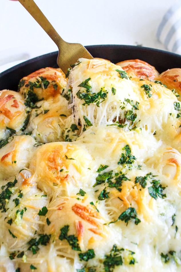 Golden fork pulling up garlic cheesy bread.