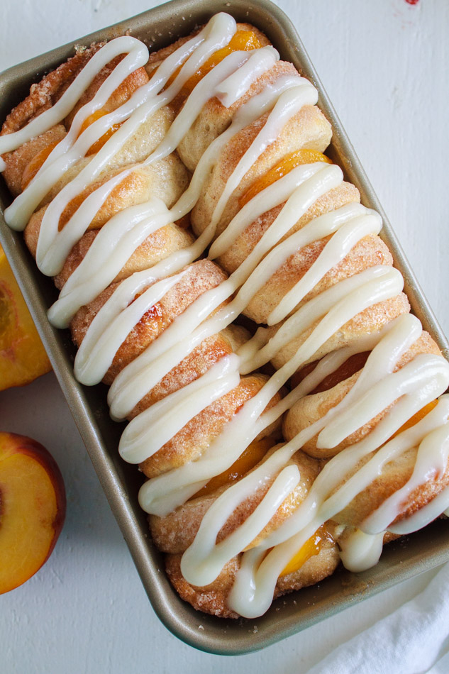 Peaches and Cream Pull Apart Bread   recipe with a sweetened Cream Cheese Glaze in a loaf pan.