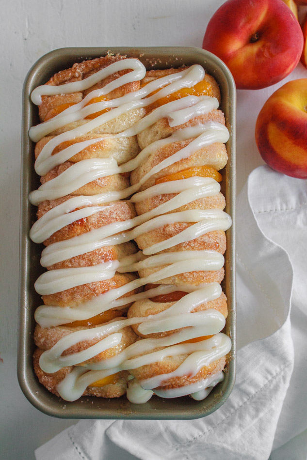 Peaches and Cream Pull Apart Bread with Cream Cheese Glaze in a loaf pan.