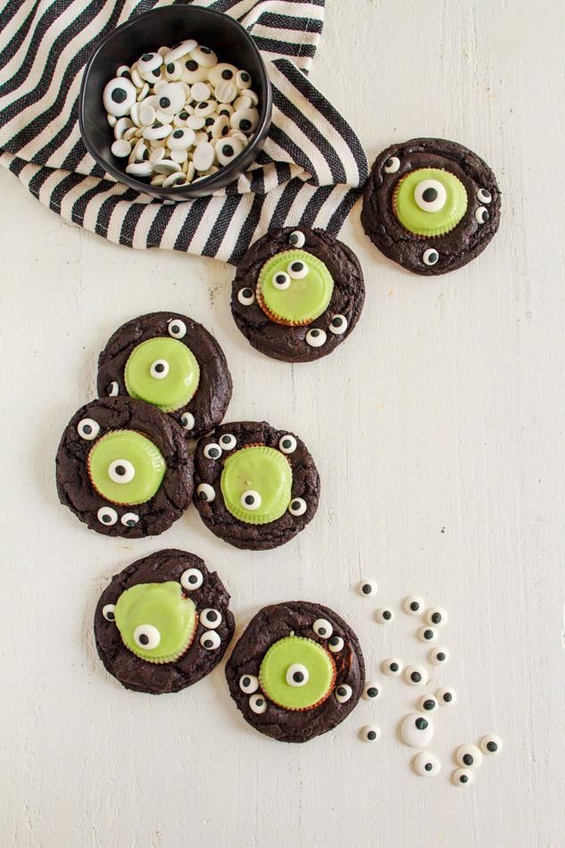 Halloween Monster Cookies are a fun and spooky treat.  Fudgey cookies full of chocolate flavor and black coco powder.  They are then embellished with Googley Candy Eyes and finished off with a Reese's Peanut Butter Franken Cup.